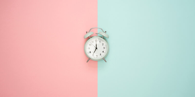 Alarm clock on pink and blue background
